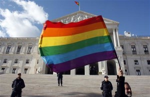 Man holds a rainbow flag in front of Portuguese Parliament after bill was passed to legalise same-sex marriages in Lisbon